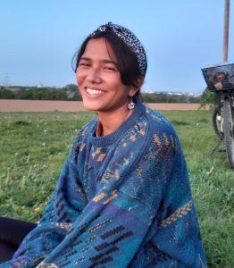 Kolumnistin Sanja sitzt auf einer Wiese. Sie trägt einen blauen Pullover mit buntem Muster und lächelt in die Kamera.