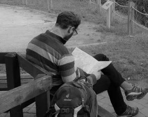 Kolumnist Franz von hinten, das Foto ist schwarzweiß, er sitzt auf einer Bank und liest eine Karte
