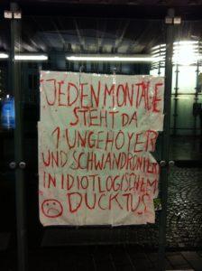 """Ein Plakat, darauf steht: """"Jeden Montage steht da 1 Ungehoyer und schwandroniert in idiotlogischem Ducktus"""", daneben ein trauriger Smiley"""