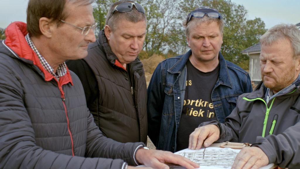 """Edwin, Klaus, Markus und Hans-Harald stehen nebeneinander, halten eine Karte in den Hän-den und blicken darauf. Sie sind die """"Vier von der Stange"""" und planen den Bau des Neubau-gebiets."""