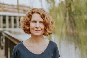 Nahaufnahme von Nina Treu mit dem Kanal und Bäumen im Hintergrund
