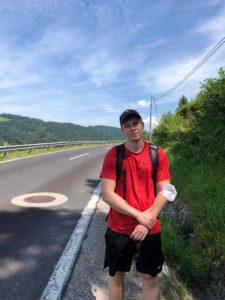 Kolumnist Leon steht beim Wandern an einer Straße, im Hintergrund die Hügel des Alpenvorlands.