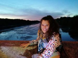 Hanna Stoffregen sitzt auf einer Brücke bei Nacht. Hinter ihr ein Fluss.