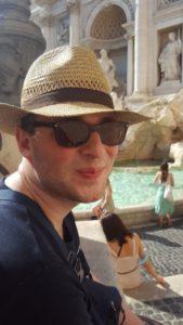 Franz sitzt mit Strohhut und Sonnenbrille in der Sonne vor einem Brunnen.