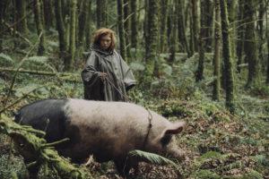 Léa Seydoux aka die Anführerin der Loner führt ein großes Hausschwein durch den Wald. Sie hat rote Haare und trägt ein grünes Regencape.