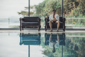 David sitzt in einem Ledersessel an einem Indoor-Pool, an seiner Seite ein Glas Orangensaft. Er trägt Badeshorts, Flipflops und ein offenes weißes Hemd.