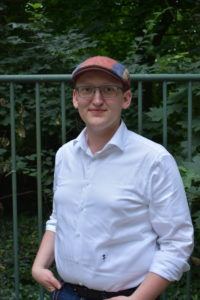 Thomas Linke trägt eine Mütze, die weder altmodisch noch hipp ist. Im weißen Hemd steht er vor einem grünen Eisenzaun. Dahinter Blätter von Bäumen: unter anderem Ahorn.