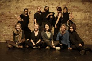Das gesamte Team hinter der Inszenierung, in schwarz gekleidet vor einer Backsteinwand lehnend.