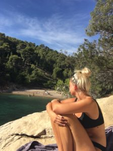 Kolumnistin Leoni sitzt in einem schwarzen Bikini auf einem Felsen, die Arme um die angezogenen Knie geschlungen, und schaut auf das Meer, den Strand und den umgebenden Wald.